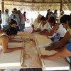 """Mujeres hondureñas de la comunidad rural del Venado reciben una capacitación por parte de técnicos chilenos para construir e instalar """"ollas mágicas""""."""
