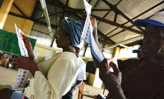 2005年10月的一个选举投票日,西非国家利比里亚西北部的蒙特塞拉州,选民正在查看选票。