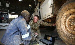 Капрал Хезер Маккуин работает автомехаником и заведует транспортными средствами ООН в Малакале, Южный Судан. На фото Хезер говорит с Ангело, местным коллегой, который помогает ей присматривать за машинами. Хезер учит Ангело, как нужно чинить автомобиль; он же передает ей ценные знания о том, как местный климат и дорожные условия надо учитывать  при уходе за машинами.