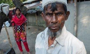 孟加拉国农民努鲁·哈克(Nurul Haque)站在他13岁的女儿前面。他说,他可能不得不让女儿辍学,嫁给一个年长的男人,因为他几乎没有别的经济选择。