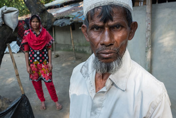 Farmer Nurul Haque stands near his 13-year-old daughter in Bangladesh, saying he may have to pull her from school and marry her off to an older man because he has few financial options left.