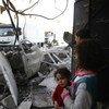 Residentes em Ghouta Oriental, na Síria, observam comboio de ajuda humanitária chegar à cidade de Douma.