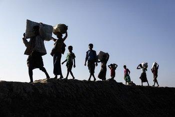 Des Rohingyas arrivés par bateau à Shah Porir Dwip, au Bangladesh, se dirigent à pied avec leurs biens vers un centre d'enregistrement et de distribution d'aide aux réfugiés établi à Teknaf, dans la région de Cox's Bazar.