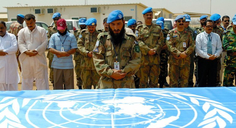 Private Johar Nafees (centre), a member of the Pakistani contingent of the UN Mission in Sudan (UNMIS), leads a prayer during the farewell ceremony in Khartoum for Sergeant Nazir Ahmed, who died in the line of duty in October 2006.