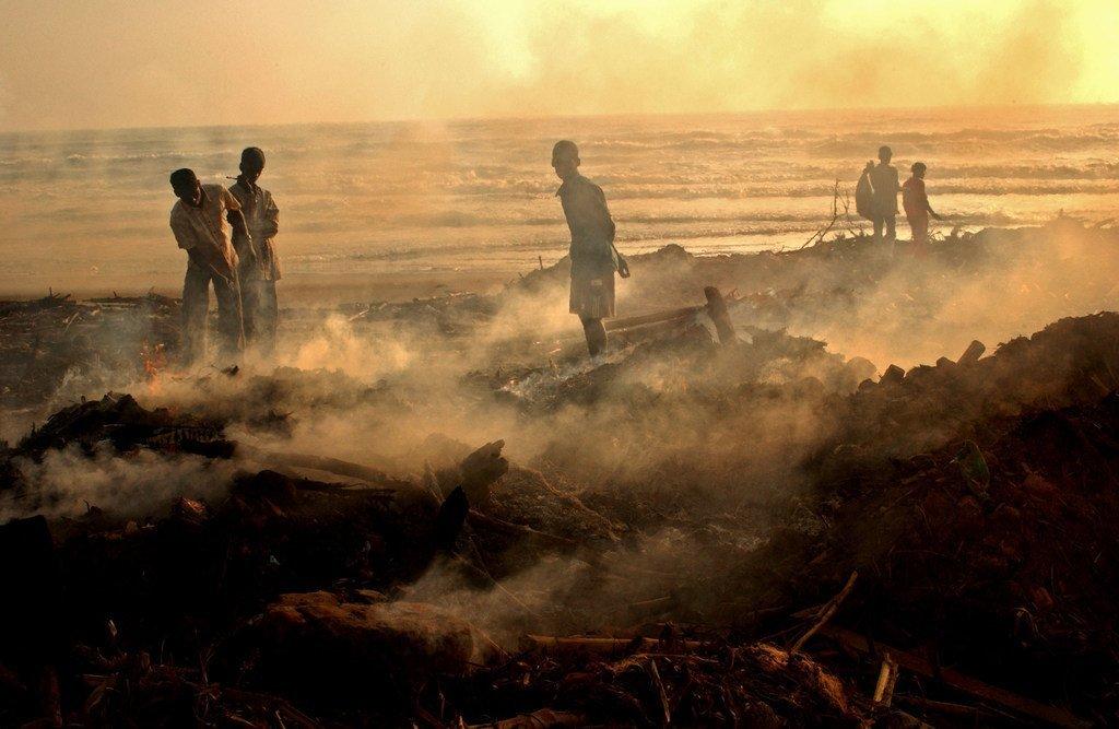 2004年印度洋海啸后,印度泰米尔纳德邦沿海的渔民仔细检查村庄的残骸。
