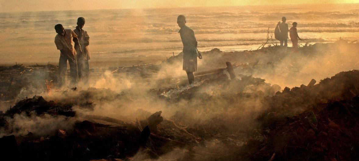 Coastal fisherfolk in Tamil Nadu, India, sift through the wreckage of their village following the 2004 Indian Ocean Tsunami.