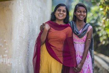 Duas adolescentes na índia posam para fotos em frente ao vilarejo onde vivem.
