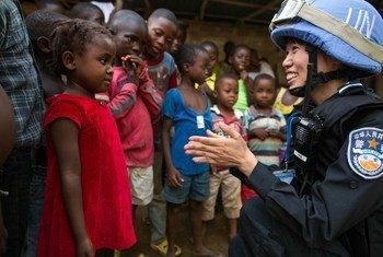 Miembro de la Misión de la ONU en Liberia comparte con una niña en el campamento de Steward, antes de terminar su mandato.