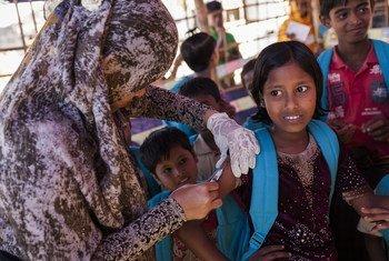 Cox's Bazar, Bangladesh: un agent de santé inocule une fillette rohingya dans le camp de réfugiés de fortune d'Unchiprang lors d'une campagne de vaccination contre la rougeole soutenue par l'UNICEF