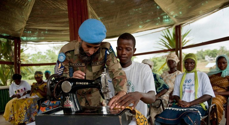 A Pakistani peacekeeper teaching a young Liberian to sew as part of the programme offered in Tubmanburg in May 2010.
