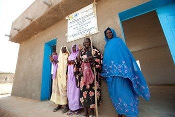 """2012年,几名妇女在由非洲联盟—联合国达尔富尔混合行动修建的妇女中心门前。妇女中心是混合行动开展的六项""""快速影响计划""""之一,涉及教育、卫生、健康、社区发展和女性赋权等多个方面。"""