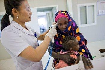 Mhudumu wa Afya kutoka Mongolia akitoa huduma kwa mama na mtoto Darfur,Sudan(10 Disemba 2012)