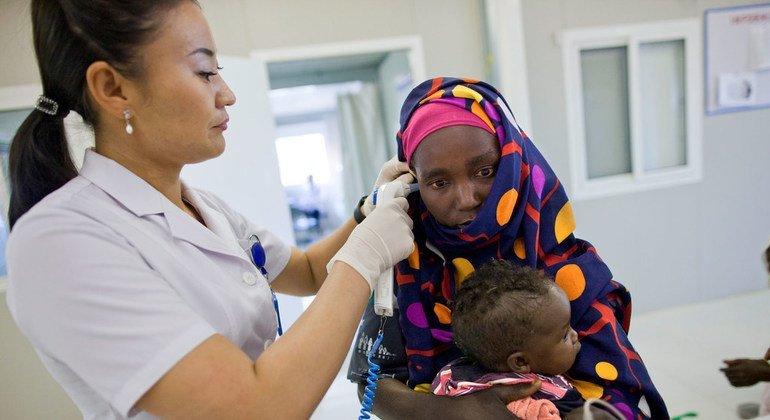 Медсестра в монгольском госпитале в Дарфуре осматривает мать с ребенком (10 сентября 2012 года)