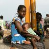 Imani, de 22 anos, espera por transporte em Sebagoro, Uganda, depois de fugir da violência na República Democrática do Congo.