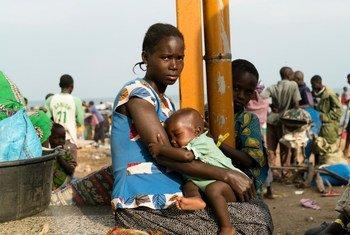 Imani, 22 ans, attend de monter dans un bus à Sebagoro, en Ouganda, après avoir fui la violence en République démocratique du Congo (RDC)