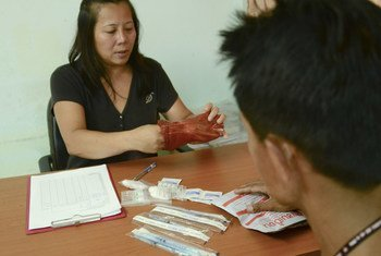 A volunteer providing clean needles to a drug user in Thailand.