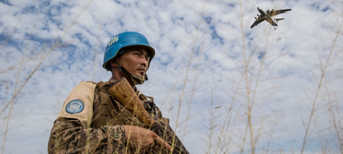 A Mongolian peacekeeper provides security as the World Food Programme drops food in Bentiu, South Sudan (21 October 2015).
