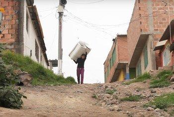 Jessica Hernández transporta sobre su espalda una de las lavadoras que alquila a los vecinos de Soacha, Colombia