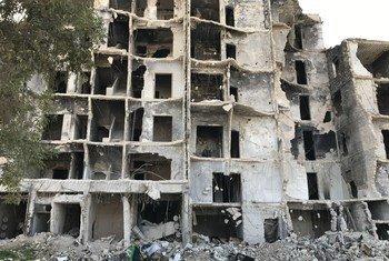 一名男孩走在叙利亚东阿勒颇被摧毁的住宅群中。