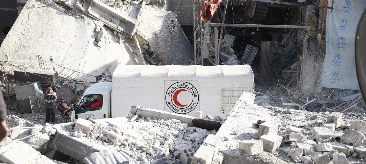 Un camión del convoy de la ONU y la Media Luna Roja pasa entre los edificios destruidos de Guta, Siria.