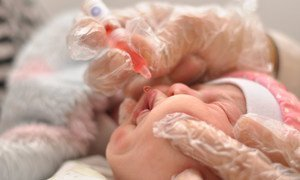 Trabajadores sanitarios vacunan a un bebé contra el sarampión.