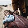 رجل يحمل طفله داخل حقيبة متجها إلى حمورية حيث فتح ممر للخروج من الغوطة الشرقية -بيت ساوا 15 مارس /آذار 2018