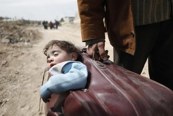 A man carried a child in his suitcase as he fled eastern Ghouta in 2018.