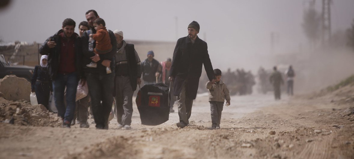 On 15 March 2018 in Beit Sawa, eastern Ghouta. families walk towards Hamourieh where an evacuation exit from Eastern Ghouta has been opened.