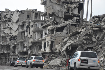 In this file photo, a convoy of UN humanitarian vehicles moves through the war-ravaged city of Homs. While aid access has improved in parts of Syria, millions of civilians remain dependent on cross-border deliveries of food and other aid.