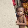Ребенок у стены дома в сельской местности в Бангладеш