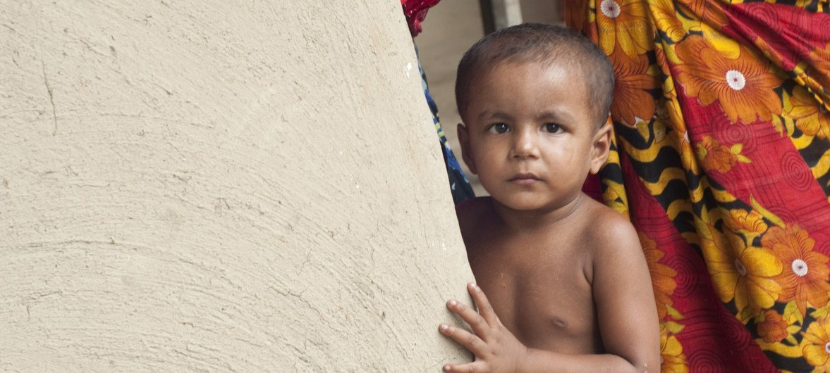 A child stands beside a wall at his family's home in rural Bangladesh.