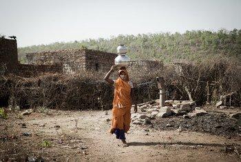 Une femme en Inde portant de l'eau jusqu'à chez elle.
