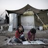 Seated on a rug atop the dirt ground, two girls complete homework outside their tent home, in the Kawergosk camp for Syrian refugees, west of Erbil, Iraq.