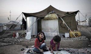 Des fillettes font leur devoir à l'extérieur de la tente qui leur sert de maison dans le camp de Kawergosk pour réfugiés syriens près d'Erbil, dans la région du Kurdistan, en Iraq.