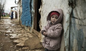An 18-month-old toddler stands outside a tent where she lives with her family in Saadnayel Camp, an informal tented settlement where Syrian refugees are sheltering, in the Bekaa Valley, Lebanon.
