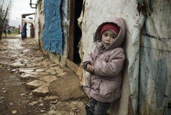 一名18个月大的叙利亚难民儿童站在黎巴嫩的一个避难帐篷外。
