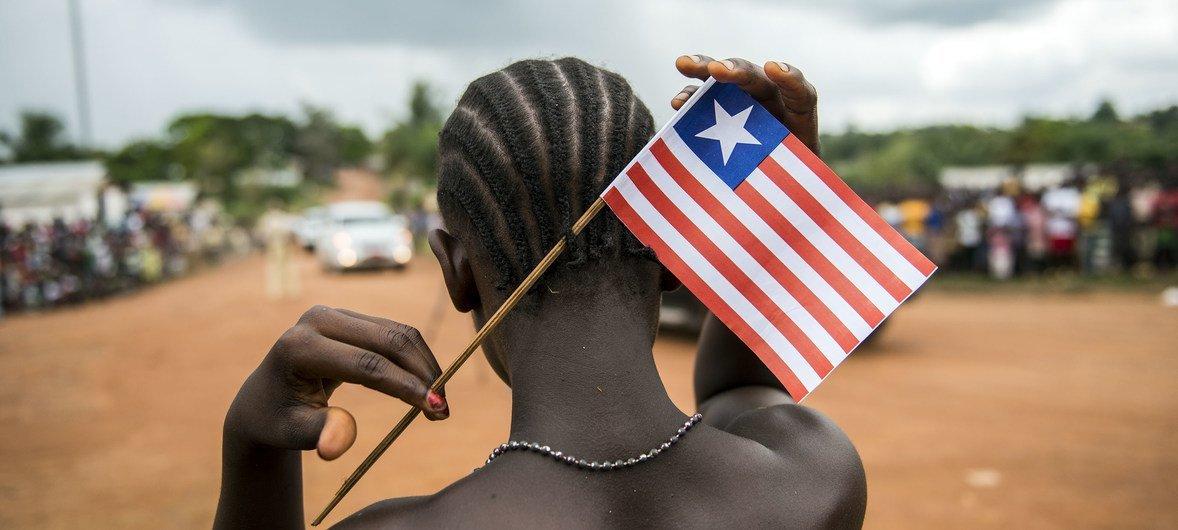 Une femme libérienne avec un drapeau du Libéria dans ses cheveux.