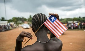 A young Liberian woman puts a flag of Liberia in her hair. The youth account for almost two-thirds of the country's population.