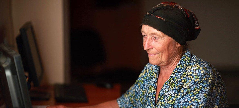 Женщина в Грузии осваивает работу с компьютером.