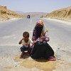 Suad de 18 años pide ayuda en una carretera de la capital de Yemen con su sobrino de 4 años, cuya madre murió en el conflicto.
