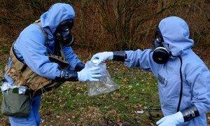 禁化武组织调查员身穿防护服,在模拟演习中收集样品。