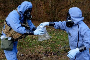 OPCW inspectors, in full protective gear, collecting samples during a mock exercise.