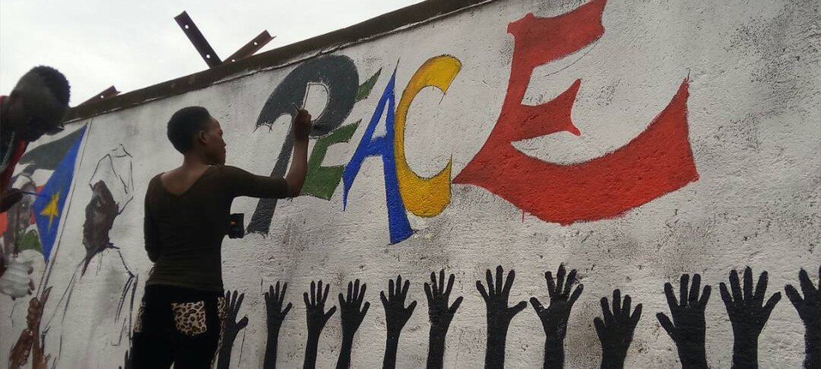 A woman paints a mural on a wall in Yei, South Sudan. As a part of a collective effort, the group of painters painted a number of pictures and messages on peace and harmony at many locations in the town.