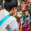 A UNICEF health official gives safe drinking water and oral retardation salts to a mother for her one-year-old child suffering from diarrhoea. They are living at temporary shelter along with at least 600 other persons after their homes were destroyed in the Papua New Guinea earthquakes.