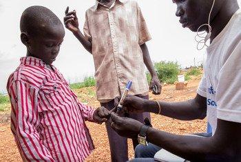 Un trabajador sanitario marca a un niño que ha recibido una vacuna contra el cólera en Sudán del Sur.