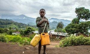 Un jeune garçon avec des récipients va chercher de l'eau sur le site de déplacés de Minova, dans le Sud-Kivu, en République démocratique du Congo.