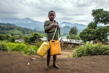 刚果民主共和国南基伍省的一处境内流离失所者营地内,一名男童正挑着水桶前去汲水。