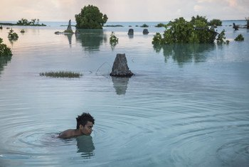 A 16-year-old child swims in the flooded area of Aberao village in Kiribati. The Pacific island is one of the countries worst affected by sea-level rise.