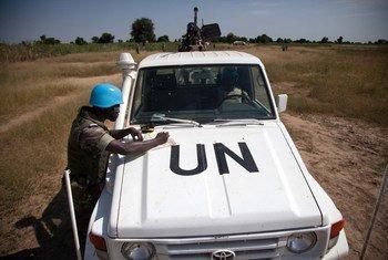 Un Casque bleu de la MINUAD originaire du Burkina Faso, basé à Forobaranga, dans l'ouest du Darfour (Soudan), vérifie une carte lors d'une patrouille vers le village de Tamar, en octobre 2013.