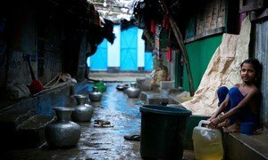 A Rohingya refugee child sits next to buckets collecting rainwater at a makeshift refugee camp in Cox's Bazar, Bangladesh. With the arrival of rains, the challenges have multiplied for hundreds of thousands of refugees in the area.
